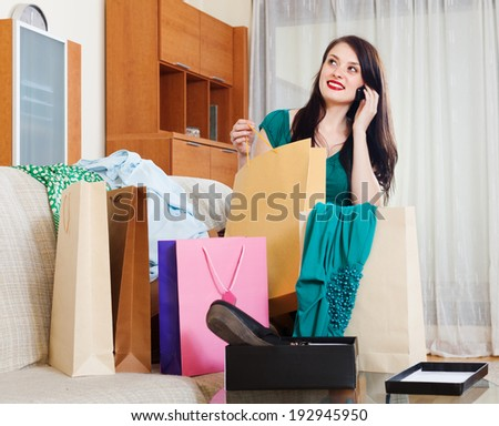 brunette woman looking purchases and speaking by mobile  at  home