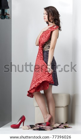 brunette woman looking red dress in the mirror