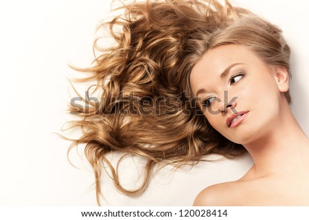 brunette woman lying on sofa and talking by cell phone - stock photo