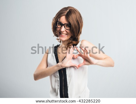 Brunette woman making a heart with her hands