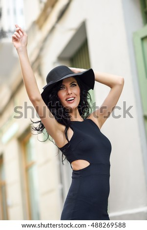 Brunette woman, model of fashion, wearing black seductive dress and sun hat in the street. Young girl with curly hairstyle walking in urban background