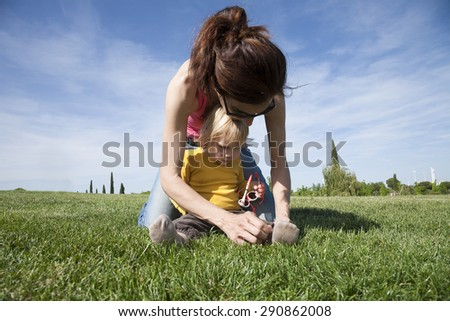 brunette woman mother tying shoelaces to two years aged blonde baby with yellow shirt with white kid sunglasses sitting on green grass lawn in park - stock photo
