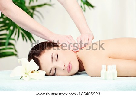 Brunette woman on neck massage in spa center