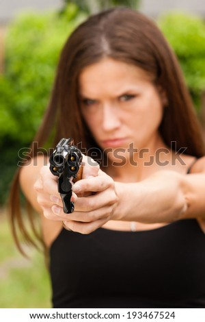 Brunette Woman Points Gun Spent Chamber Ready to fire - stock photo
