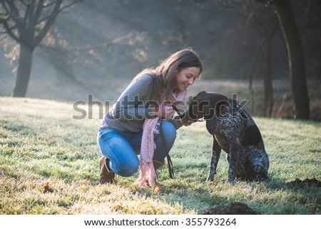 Brunette woman posing with her adorable German pointer dog outdoor - stock photo