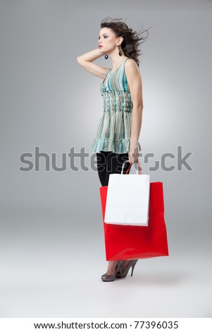 brunette woman shopping red white bags wind