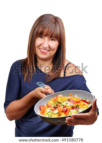 Brunette woman showing pan full of vegetables isolated