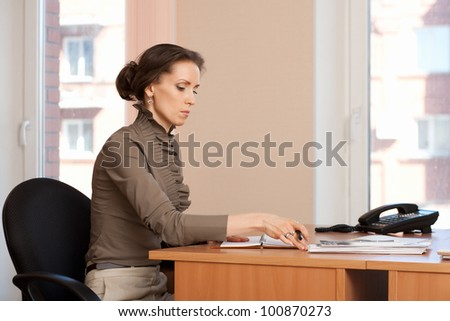 Brunette woman sitting at a table in the office,  and handle makes notes in a diary