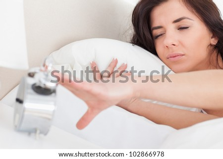 Brunette woman turning off her alarm clock in her bedroom