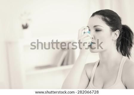 Brunette woman using asthma inhaler in living room - stock photo