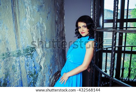 brunette woman wearing a blue dress in the room with old walls and furniture - stock photo