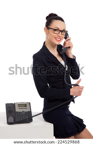 brunette woman wearing black skirt and jacket talking on the phone and sitting on cube over white background  - stock photo