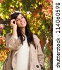 Brunette woman wearing coat and wool cap on autumn leaves background - stock photo