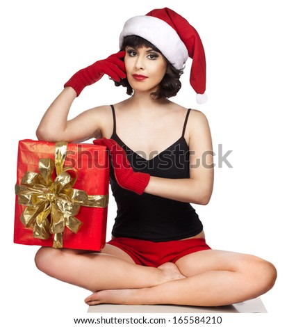 brunette woman wearing santa hat  holding  Christmas gift - stock photo
