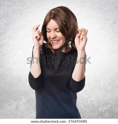 Brunette woman with her fingers crossing