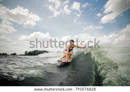Brunette woman with wet long hair riding wakeboard on high wave having fun and spiting out spray
