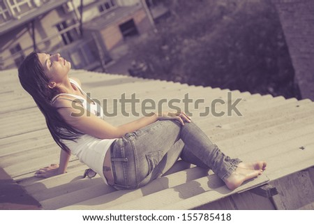 brunette women sit on the roof of the building, vintage toned image, summertime freedom concept