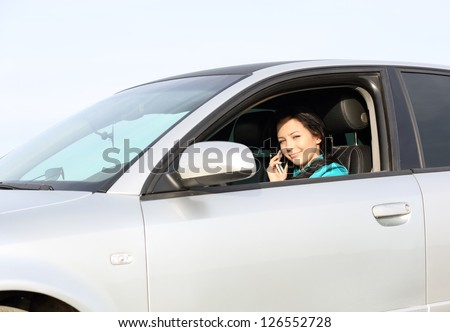 Brunette young girl driving a car on the phone - stock photo