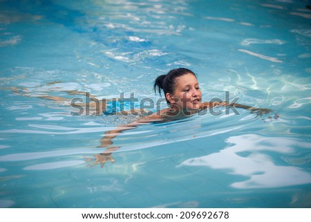 brunette young girl in blue swimming suit swim in blue water in the swimming pool with her reflection in it - stock photo