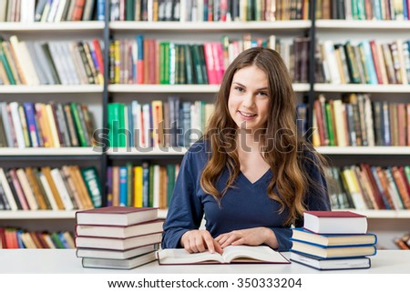 brunette young girl sitting at a desk in the library with piles of books on both sides of the desk reading, looking in front of her, a concept of studying, blurred books at the back - stock photo
