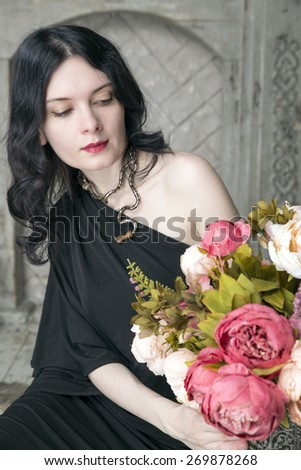 Brunette young woman in black dress with flowers. Selective focus on her face - stock photo