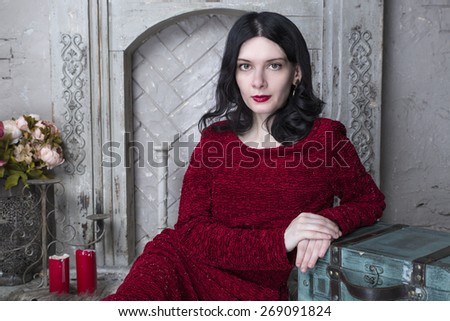Brunette young woman in red dress sitting near the fireplace - stock photo