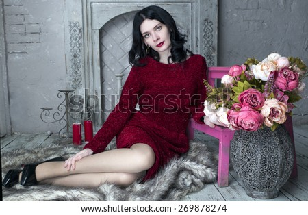 Brunette young woman in red dress sitting near the fireplace with flowers - stock photo