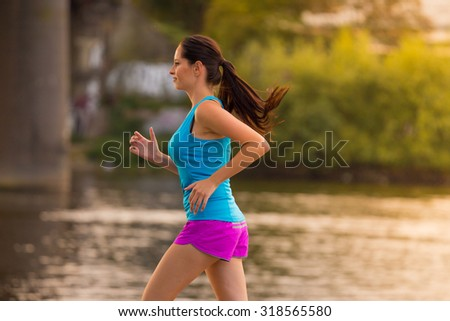 Brunette young woman running in city.   - stock photo
