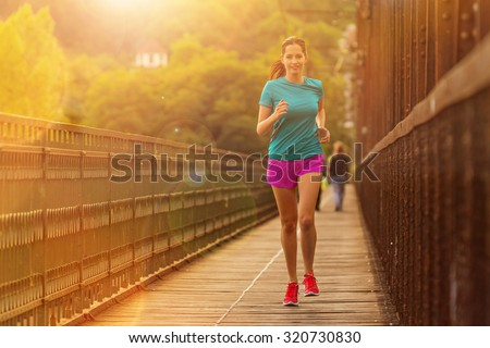 Brunette young woman running in city.