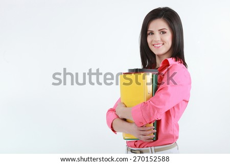 Brunette young woman with colorful folders isolated on white - stock photo