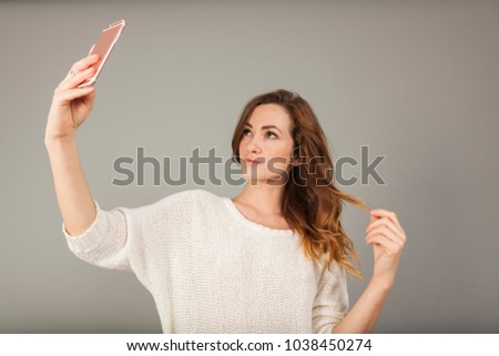 brunette young womenwith a pink cellphone doing a video call on grey background