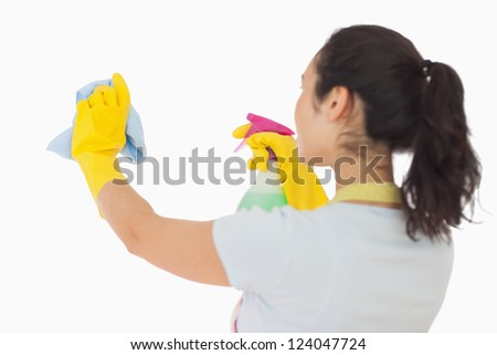 Brunetter woman spraying and wiping in rubber gloves - stock photo