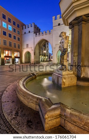 Brunnenbuberl Fountain and Karlstor Gate in the Evening, Munich, Germany - stock photo