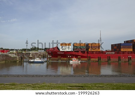 BRUNSBUETTEL, GERMANY - JUNE, 7. The container vessel Amerdijk at the lockage Brunsbuettel (Schleswig-Holstein, Germmany) to the Kiel Canal as entering the newly repaired lock chamber on June 7, 2014.