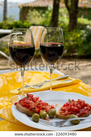 Bruscheta and red wine glasses over Chianti landscape in Tuscany.