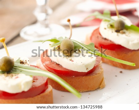 Bruschetta canapes with tomatoes, capers and mozzarella on wooden table. Shallow focus.