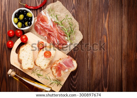 Bruschetta ingredients - prosciutto, olives, tomatoes. Top view on wooden table - stock photo