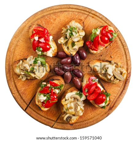 Bruschetta is usually served as a snack or appetizer. The most popular recipe outside of Italy involves basil, fresh tomato, garlic and onion or mozzarella.  - stock photo