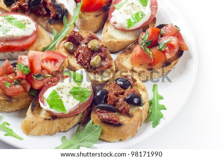 bruschetta, mozzarella, dried tomatoes... - stock photo