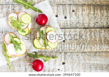Bruschetta with cottage cheese, radish, cucumber and arugula. Copy space. Top view - stock photo