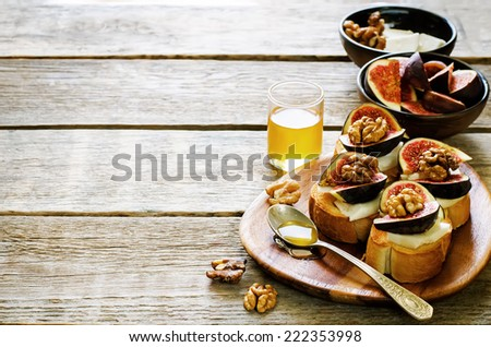 bruschetta with figs, honey, goat cheese and walnuts on a dark wood background. tinting. selective focus on walnut on the right bruschetta - stock photo