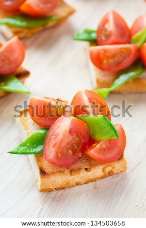 Bruschetta with fresh tomato and snow peas, selective focus