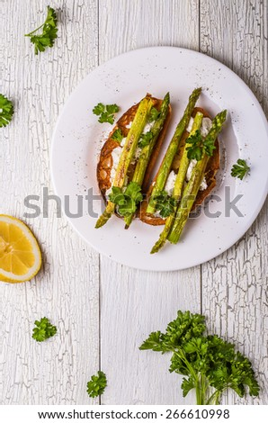 Bruschetta with goat cheese and grilled asparagus on a white wooden background. - stock photo