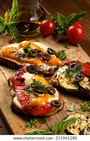 Bruschetta with grilled bell pepper, zucchini, black olives, mozzarella cheese and herbs - stock photo