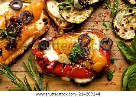 Bruschetta with grilled bell pepper, zucchini, olives and mozzarella cheese. Vegetarian dish - stock photo