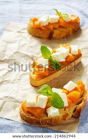 bruschetta with honey pumpkin and goat cheese on a blue background. tinting. selective focus on mint on the bottom bruschetta - stock photo