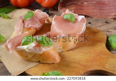 bruschetta with prosciutto and basil leaves