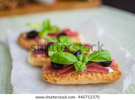 Bruschetta with prosciutto, olives and basil. Delicious sandwich.  Italian appetizer. Selective focus. - stock photo
