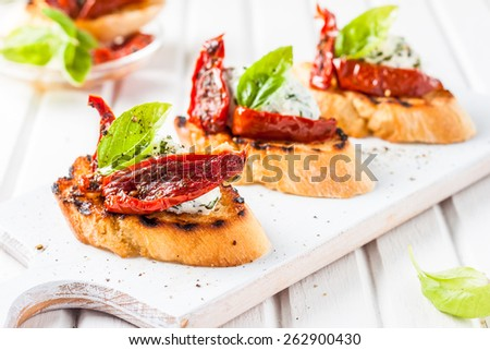 Bruschetta with rikkota, basil and sun-dried tomatoes on a light wooden background - stock photo