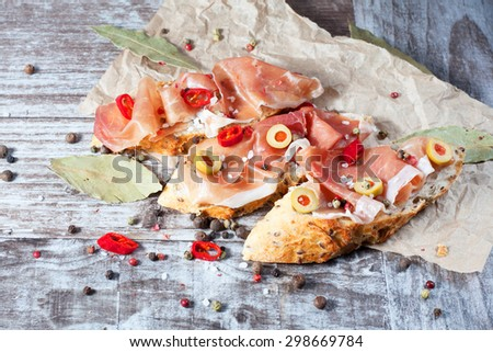 Bruschetta with roasted bell pepper, prosciutto, garlic, olives, spices and herbs. Appetizers. Tapas. - stock photo